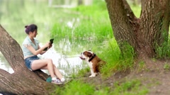 Asian woman taking dog's photo in the park Stock Footage