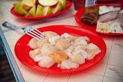Scallop purified in a red plate Stock Photos