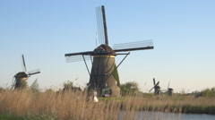 CLOSE UP: Beautiful antique Dutch mills on vast dried grassy field next to river Stock Footage