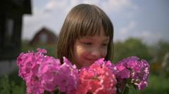 Little Girl gets pleasure from flowers Stock Footage