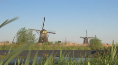 Small bridge leading over water canal to vast field of traditional Dutch mills Stock Footage
