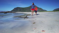 A mother and her son walking on a beach in Lofoten, Norway with some starfish vi Stock Footage