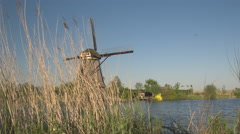 CLOSE UP: Stunning authentic vintage windmill on the river bank turning blades Stock Footage