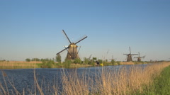 Scenic view of old antique Dutch windmills on vast grass field from riverbank - stock footage
