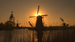 Stunning authentic old windmill on the river bank at beautiful golden evening Stock Footage
