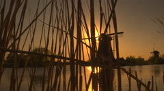 Stunning authentic old windmill on the river bank at beautiful golden morning Stock Footage