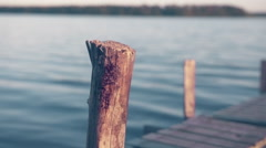 Water Drops from Female Hand on Wooden Jetty Pole Summertime - Graded Stock Footage