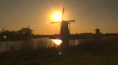 Stunning authentic old windmills on the river bank at beautiful golden sunset Stock Footage