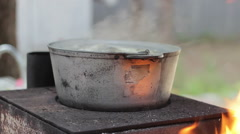 Cooking soup of fish in a metal pot on a wood-burning stove with an open fire - stock footage