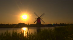 Beautiful authentic old windmill on the river bank at beautiful golden sunrise Stock Footage