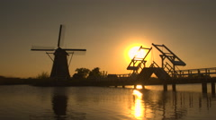 Wooden drawbridge on river with traditional windmill in background at sunset - stock footage