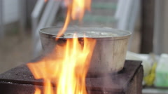 Cooking soup of fish in a metal pot on a wood-burning stove with an open fire Stock Footage