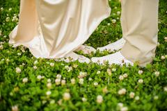 The feet of men and women in white on clover - stock photo