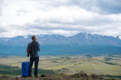 male traveler on a background of mountains - stock photo