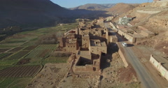 Drone footage of car moving on road in old town by mountains, High Atlas, Stock Footage
