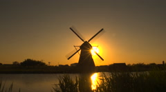 AERIAL: Amazing old traditional Dutch windmill at beautiful golden sunset - stock footage