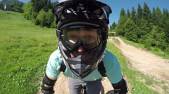PORTRAIT CLOSE UP: Young pro mountain bike rider speeding downhill in bike park Stock Footage