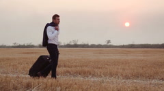 A man in a business suit comes with a travel bag on a field of harvested wheat Stock Footage