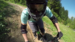 PORTRAIT CLOSE UP: Pro mountain bike rider riding downhill trail in bike park Stock Footage
