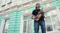 The man in the bandana and saxophone in his hands against the wall Stock Footage