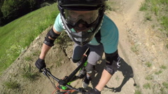 PORTRAIT CLOSE UP: Focused young downhill mountain biker riding dirt flow trail Stock Footage