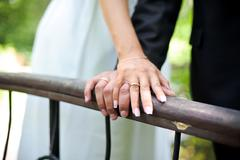 Hands of the bride and groom on the railing - stock photo