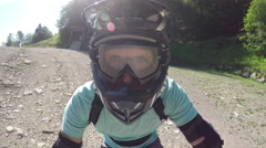 PORTRAIT CLOSE UP: Young biker starts riding downhill trail in bike park Stock Footage
