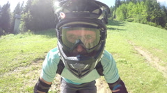 PORTRAIT CLOSE UP: Young biker riding downhill trail in dense green forest Stock Footage