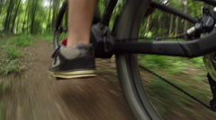 CLOSE UP: Young biker riding electric bike fast through the forest terrain Stock Footage