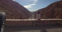 Drone footage of woman looking at rocky mountains while sitting on retaining Stock Footage