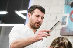 Male hairdresser puts woman's hair in a hairdressing salon Stock Photos