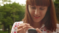 Girl surfing on the Internet in the city park - stock footage