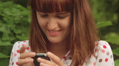 Girl surfing on the Internet in the city park and feel happy - stock footage