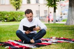 Handsome young businessman reading book lying in the park Stock Photos