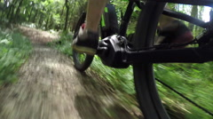 CLOSE UP: Unrecognizable man pedaling electric bike on offroad trail in forest Stock Footage