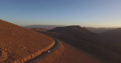 Drone footage of car moving on winding road amidst arid landscape during sunset, Stock Footage