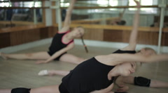 Artistic gymnasts warming up sitting on the splits Stock Footage