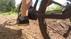 CLOSE UP: Biker man pedaling electric bike on offroad dirt track in forest Stock Footage