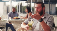 Bearded man with tall glass and pony tail Stock Footage