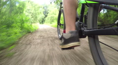 CLOSE UP: Biker riding and pedaling electric bike on gravel dirt road in forest - stock footage