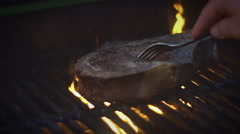 Rib Eye steak on a grill, slow motion footage Stock Footage