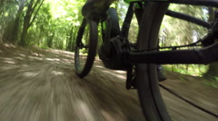 CLOSE UP: Biker riding electric bicycle fast on gravel dirt road in sunny forest Stock Footage