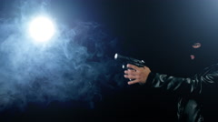 Masked gangster holding gun into smooky scene Stock Footage