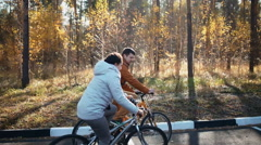 Camera tracks happy couple as they cycle along track smiling and have fun Stock Footage