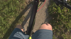 FPV CLOSE UP: Unrecognizable man pedaling electric bike along the dirt path Stock Footage
