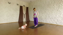 The young blonde girl practicing yoga with her child in the hall. Warm-up. 4K Stock Footage