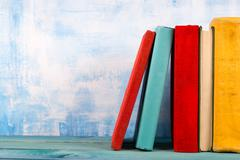 Composition with old vintage colorful hardback books, diary on w Stock Photos