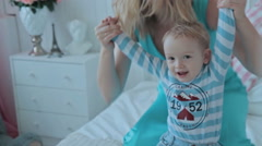 Boy with mother jumping on bed Stock Footage