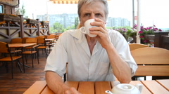 Older man sitting at table and drinking tea outdoors Stock Footage