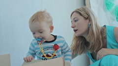 Mother give toy ship to her son Stock Footage